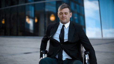 Disabled attractive invalid entrepreneur unfolds on wheelchair outdoor. Armchair on wheels. Handicapped man near glass building offices. Happy emotion portrait face middle shot