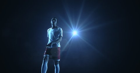4K slow motion video of a male soccer player makes a dramatic play by jumping horizontally. He kicks the ball with his feet. The background is dark behind him. Only one of the lights shine brightly.