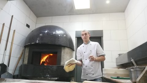 Chefs rotate pizza dough in the air.