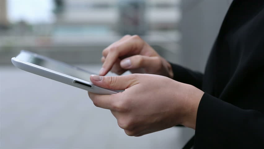 Hands of business woman using tablet computer in the city