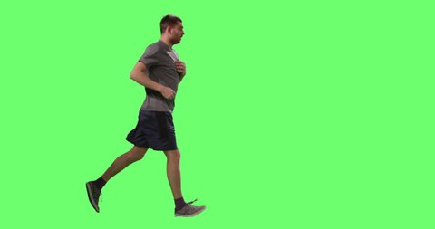 Man in a T-shirt is Jogging on a Mock-up Green Screen in the Background. Shot on RED Cinema Camera in 4K (UHD).