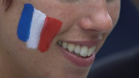 MARSEILLE, FRANCE - JUNE 15, 2016: UEFA EURO 2016. Football fans before France vs Albania game. Close up of smiling woman face painting flag of France on cheeks, make-up