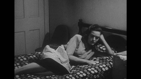 1950s: Wife lies on bed. Woman shakes her head and sits up. Woman takes off and angrily throws apron. Woman rubs her hands together.