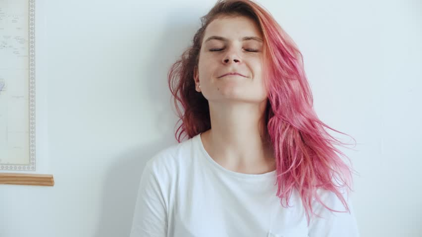Beautiful attractive female with rose pink unconventional hair, undoes her bun and let her hair fall loose, shakes it in funny and shy movement, smiles and chuckles into camera
