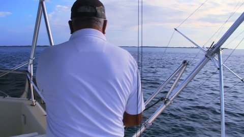 Captain extends outrigger on deep sea fishing boat.