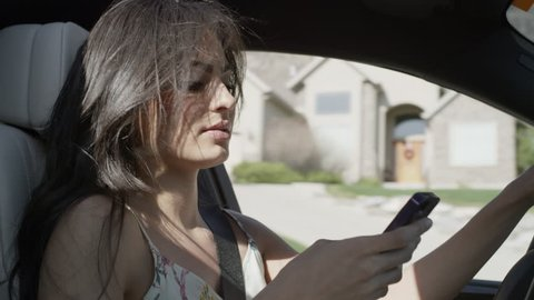 Close up of woman driving distracted with cell phone / Cedar Hills, Utah, United States