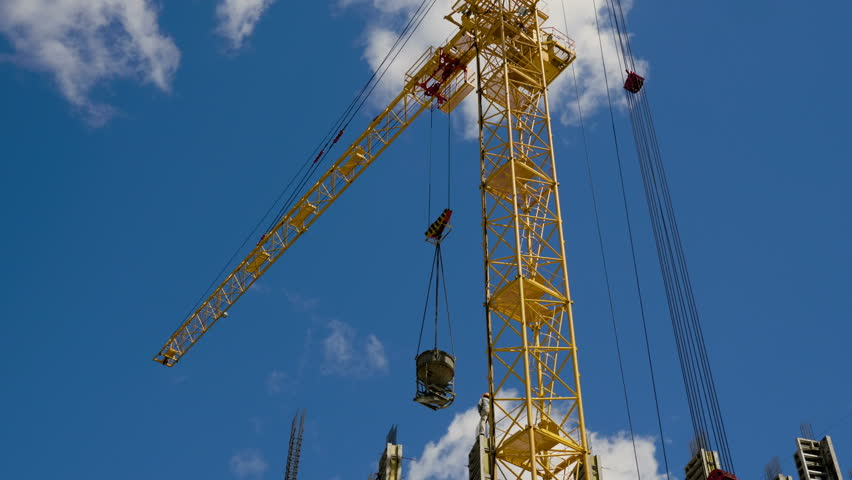 Urban growth. Construction site. Construction crane on background of blue sky. 4K