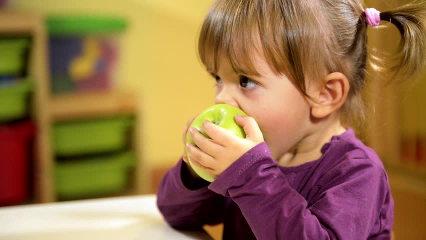 Happy children and healthy food, cute caucasian baby girl eating green apple, fruit at school. Sequence | Shutterstock HD Video #2866240