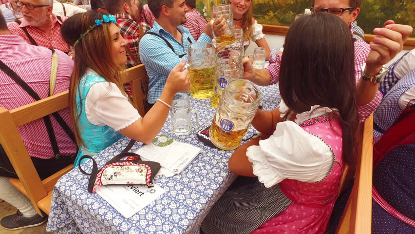 Munich, Germany-2010s: People raise their beer mugs in a toast at Oktoberfest, Germany.
