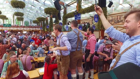 Munich, Germany-2010s: Drunken men celebrate in a beer hall during Oktoberfest in Germany.
