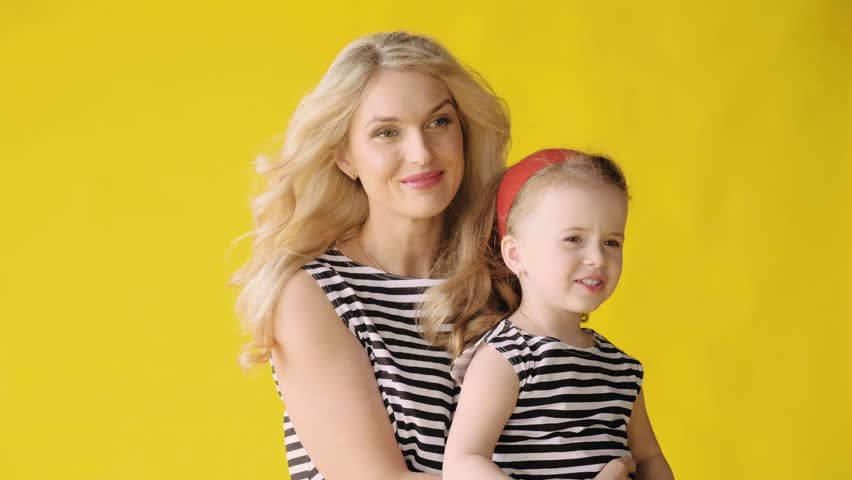 Pretty blonde woman and cute baby girl with hair developing in the wind in family photoshoot on yellow background. Medium shot. Mom and daughter in beautiful dresses and with beautiful hairstyles