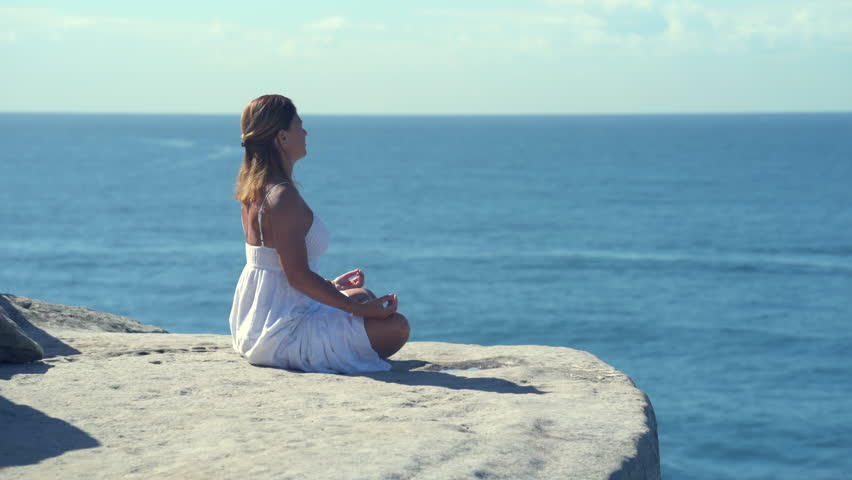 Woman sitting and  meditating on a cliff over the ocean, Yoga on the cliff edge