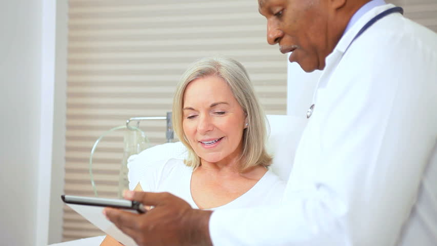 Ethnic medical consultant using wireless tablet inform senior female patient current treatment