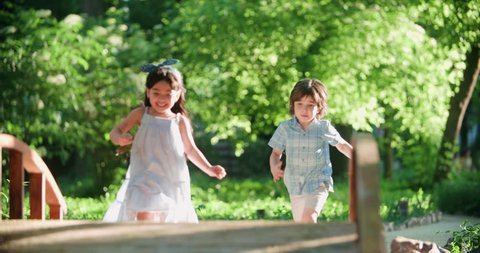 two children,a boy and a girl running in the Park, laughing happily ,slow motion