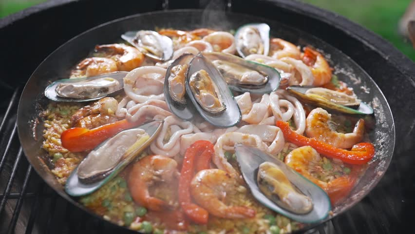 The cook makes paella on the open fire in the big hot pan, grill anf barbecue, spanish food, paella with seafood, food cooking outdoors