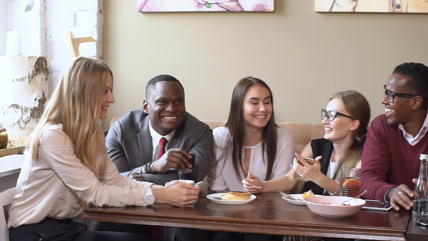 Multi ethnic people talking about work while they eating. | Shutterstock HD Video #28718119