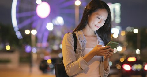 Woman working on smart phone in the city