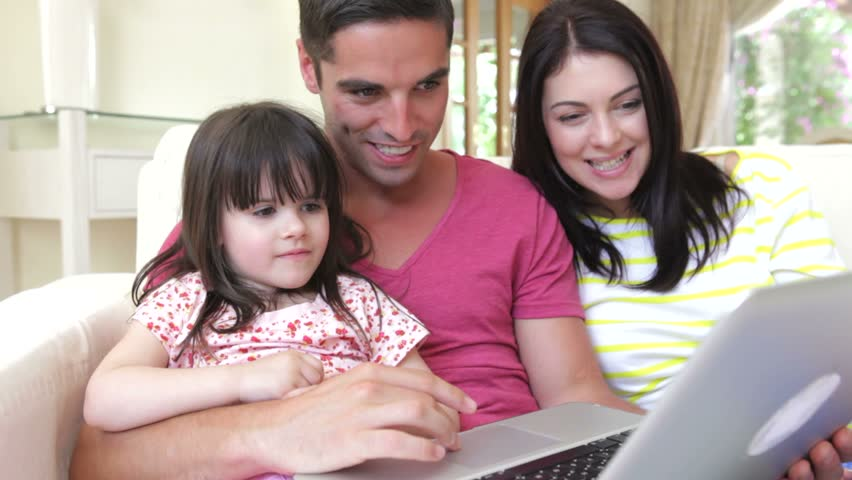 Family relaxing on sofa together looking at screen, daughter points at things of interest.