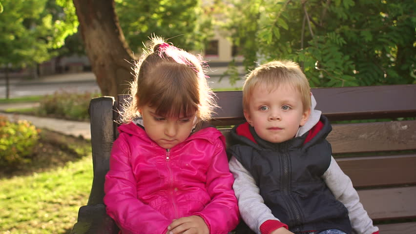 fun boy three or four years kissing sad girl outdoors during a walk in the park - Pics Of Small Children