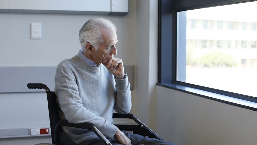 Thoughtful senior man sitting on wheelchair at hospital. Sad disabled on wheelchair at the medical center feeling lonely. Retired man alone in a medical clinic. | Shutterstock HD Video #28765780