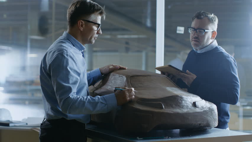 Two Male Automotive Designers Working on a Clay Model of New Generation Electric Car Future Design. One Holds Tablet Computer, Other Sculpts with Clay with Rake/Wire. Shot on RED EPIC-W 8K  Camera.