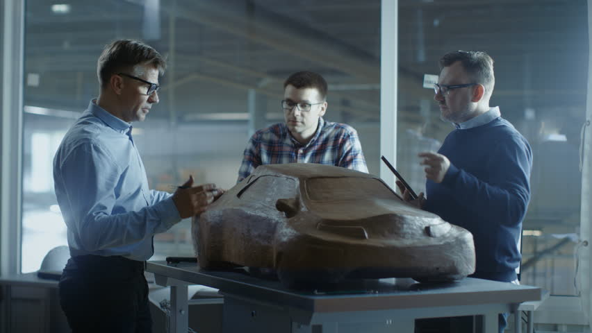 Team of Automotive Design Engineers Discusses New Prototype Design Model Made of Plasticine Clay. They Work in a Large Car Factory. Shot on RED EPIC-W 8K Helium Cinema Camera.