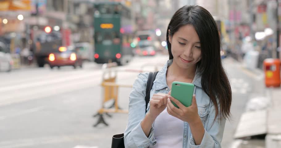 Woman using cellphone in Hong Kong city