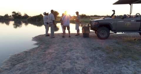 Aerial view of Tourists and guides enjoying a sundowner at the rivers edge in the Okavango  Delta at sunset