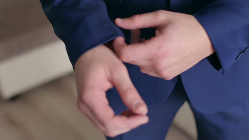 Successful man in the blue suit straightens his sleeves, close-up