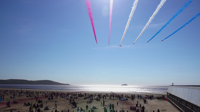 WESTON, ENGLAND - June 17: Red Arrows RAF (Royal Air Force) Airshow Display, Colored Smoke Trails over Ocean & Spectators on June 17 2017 in Weston Super Mare, England.