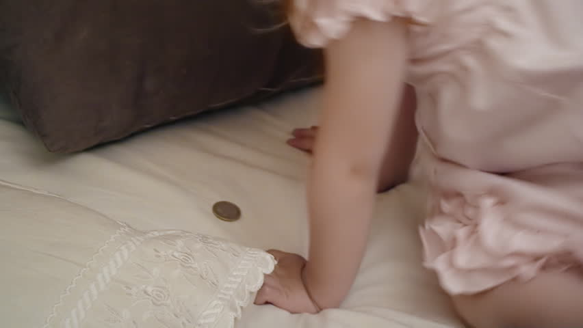 A little girl in her bed hides a coin (money) under the pillow, for the tooth fairy to find it and give back the fallen milk teeth.