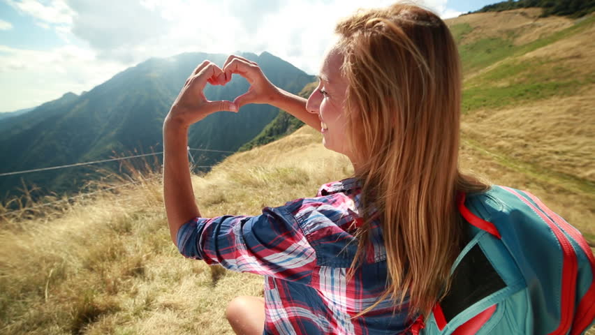 One woman making heart shape at mountain top Young woman hiker having a break sitting on the grass on the mountain top making a heart shape with her hands showing she is loving the nature.