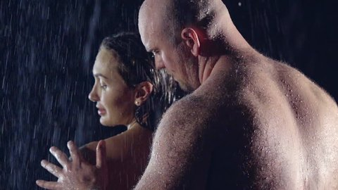 Nude man with a muscular hairy back touches his beloved woman pressed against her back with his chest. he's bald and brutal. in the darkness under the shower.