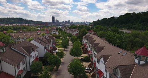 A reverse aerial establishing shot of the upscale residential homes on Washington's Landing Island with the Pittsburgh skyline in the distance.