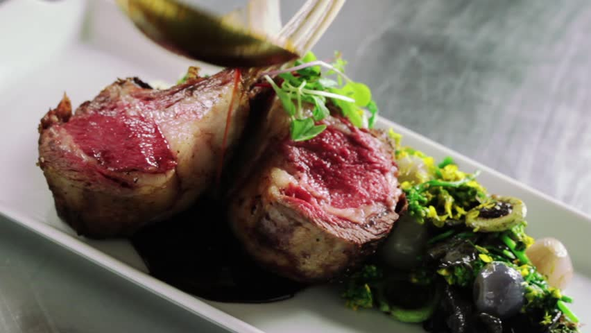 slide across a plate with lamb chops as Chef pours sauce on plate. Final touch.