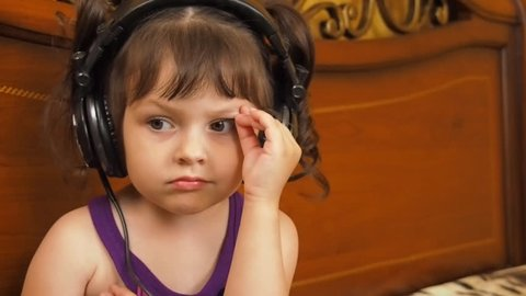 Child in headphones. A little girl listens to an audiobook.