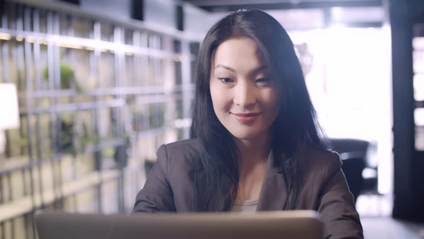 PAN of smartly dressed Asian businesswoman sitting in cafe on sunny day and typing on laptop while smiling | Shutterstock HD Video #28882120