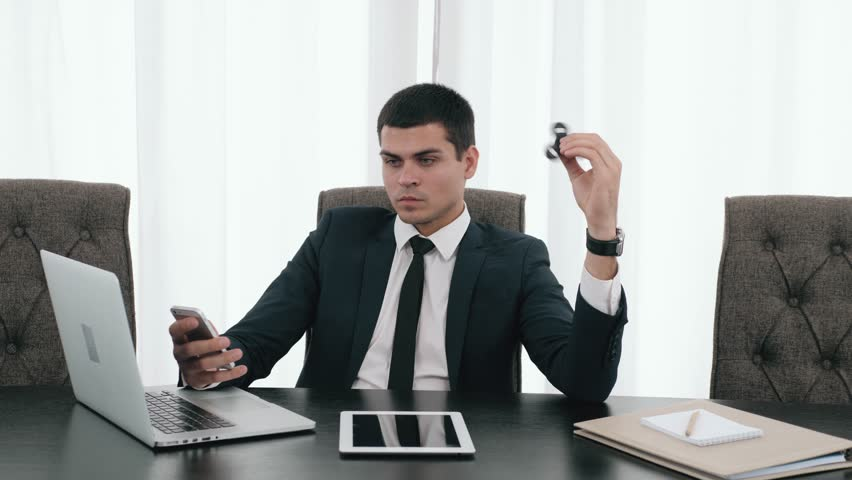 Cinemagraph Businessman with a spinner, confident director with spinner fidget, business man with laptop and tablet in modern office relax with spinner toy