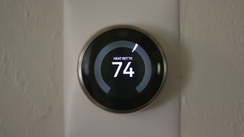 Man Increasing Temperature of Smart Thermostat Gadget At Home