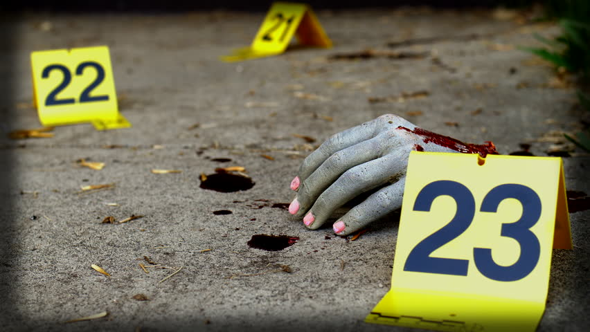 SEVERED FEMALE HAND AT A CRIME SCENE.  Slow, close up dolly shot of a bloodied female hand on a sidewalk.  Blood splatters surround the hand which has numerous crime scene markers.