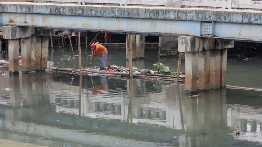 a man working in unhealthy open sewer of Jakarta