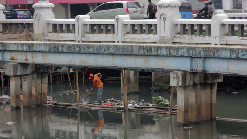 Indonesian man working in unhealthy open sewer of jakarta