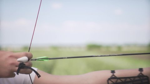 Young attractive female professional archer bends mechanic bow arrow concentrating on target on green field in close up