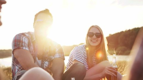 Group of young happy friends having picnic in the nature, laughing happily, chatting and toasting with bottles of beer in bright sunlight. Leisure time, summer vacation. Positive mood, true emotions.