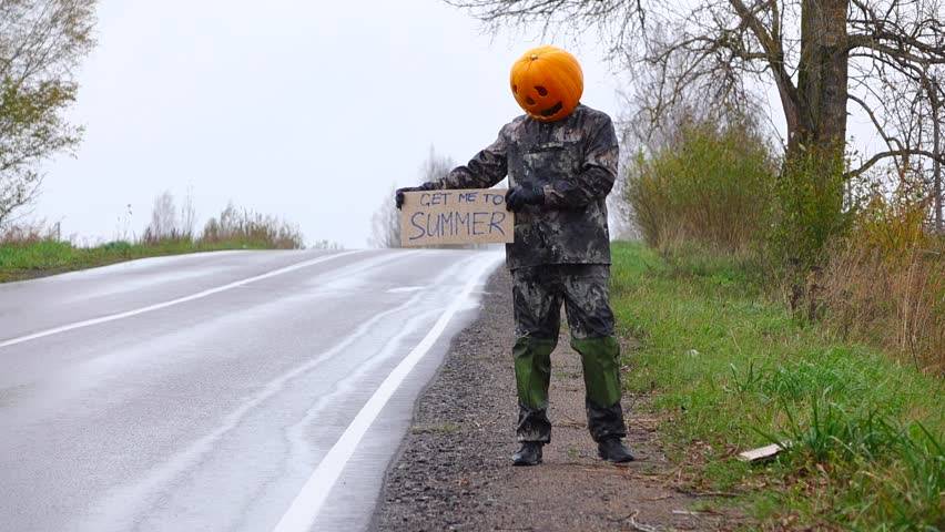 Poor pumpkinhead man stand at roadside with written sign 'get me to summer', cool and rainy autumn weather. Empty road, sad freaky person and unsuccessful hitching.