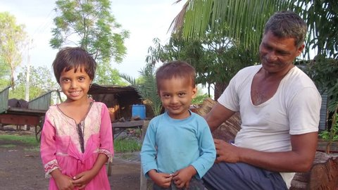 Fifty year old Indian man with grand son and daughter in the morning in rural village Salunkwadi, Ambajogai, Beed, Maharashtra, India, Southeast Asia