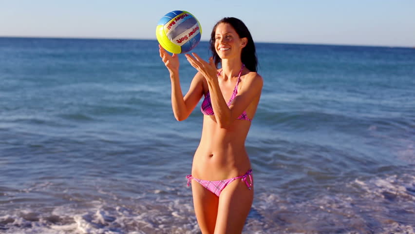 Smiling woman playing volleyball on the beach