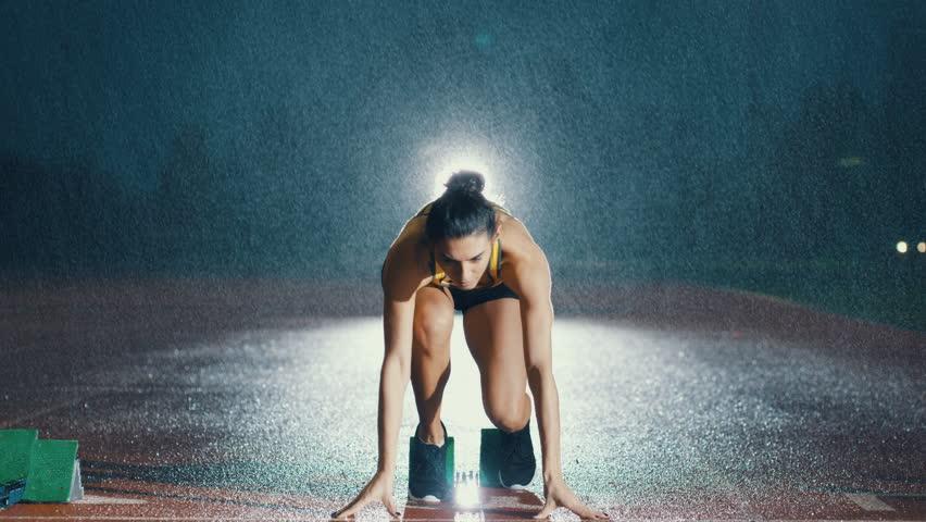 Female hispanic athlete training at running track in the dark & in the rain. Slow motion.