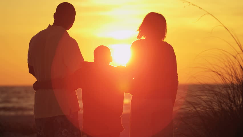silhouette of carefree african american family enjoying sunset and togetherness on beach vacation 4k stock