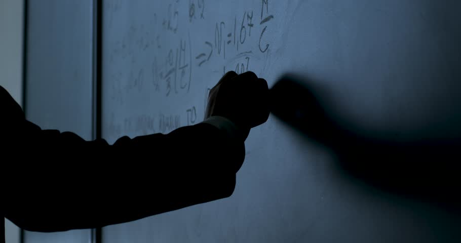 Scientist writing formulas on chalkboard. Hand with chalk wrote physics formulas on black chalkboard closeup